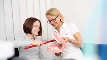 Dr. Engemann-Meyer erklärt einer jungen Patientin an einem großen Modell, wie man sich die Zähne putzt.