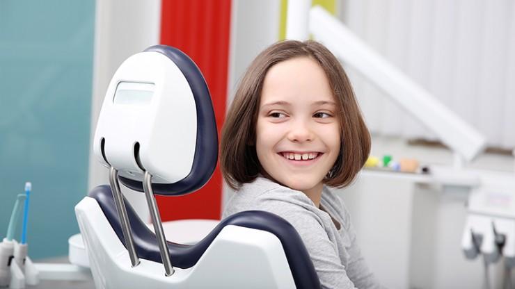 Eine junge Patientin auf dem Zahnarztstuhl.