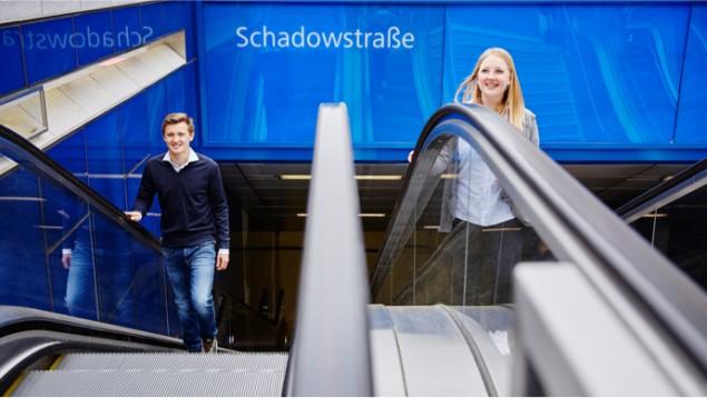 Zwei Menschen fahren Rolltreppe an der U-Bahn-Station Schadowstraße.